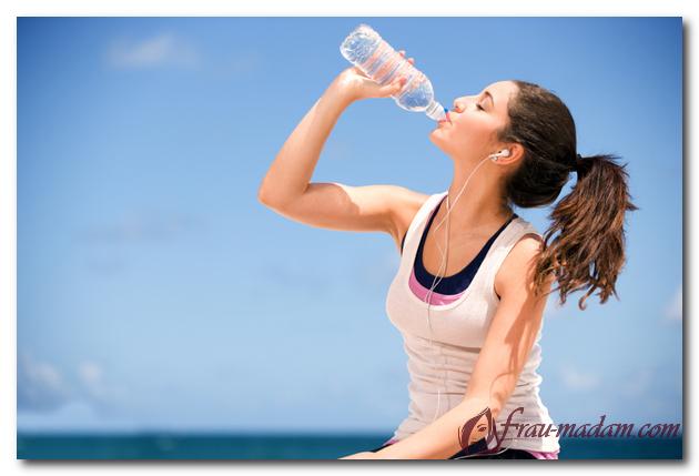спортивная девушка пьет воду из бутылки